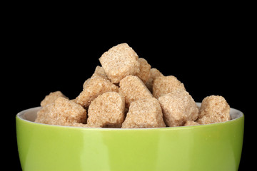 brown cane sugar cubes in bowl on black background
