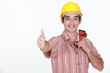 Thumbs up from a young construction worker