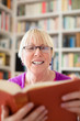 Happy senior woman with glasses reading book at home
