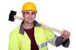 craftsman holding a huge hammer on his shoulder