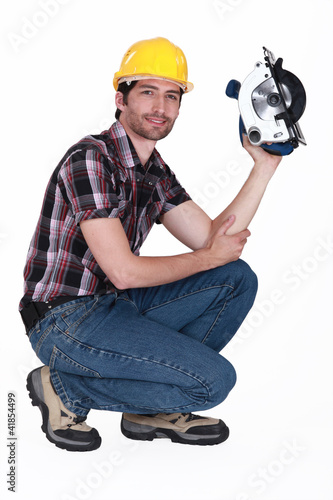 Man crouching down whilst holding circular saw