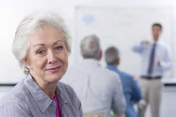 Smiling woman turning in seat during college evening class