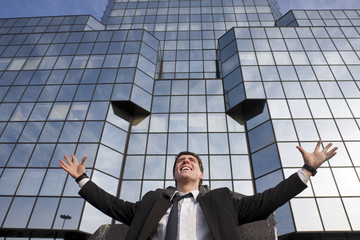 Happy young scuccessful businessman against office