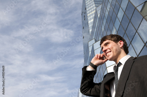 Happy young scuccessful businessman on phone against office