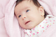 Cute baby with blue eyes lying on the bed