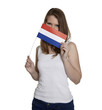 Attractive woman hides her face behind flag of the Netherlands