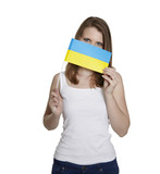 Attractive woman hides her face behind flag of Ukraine