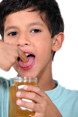 Boy tasting some honey
