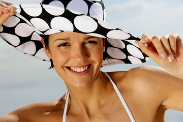 Attractive brunette wearing spotted hat at the beach