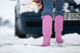 Close up of woman's feet as she pushes car through winter snow