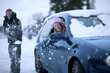 Playful man throwing snow at girlfriend sitting in car