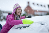 Smiling woman scraping snow from car windshield