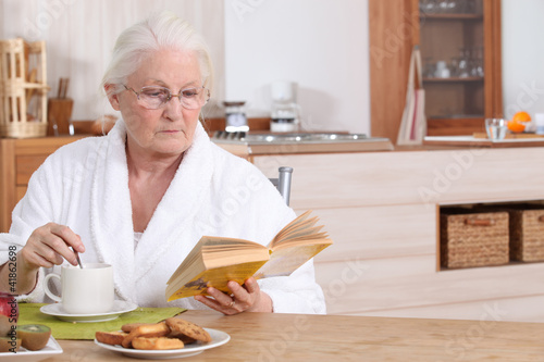 Elderly lady reading over breakfast