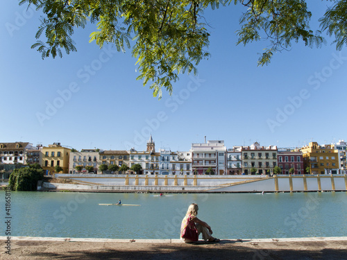 Tourist sitting on waterfront in Seville, Spain