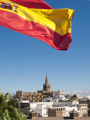 Spanish flag fluttering with cathedral in background, Seville, Spain