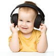 Cute little boy enjoying music using headphones
