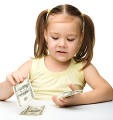 Cute cheerful little girl is counting dollars