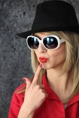 Pouting woman in sunglasses and hat