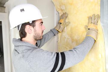 Man installing wall insulation