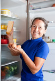 woman taking cheese of the fridge