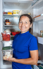 woman with  vegetables near the fridge