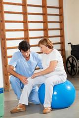 Therapist Examining Senior Woman's Knee