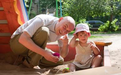 dad with  toddler  playing  in sandbox