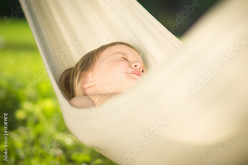 Adorable baby sleep quiet in hammock on sun
