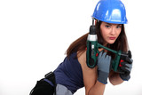 Attractive brunette posing with power drill