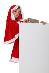 Little girl in a Santa outfit with a board for your message