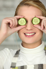 blonde wearing apron hiding eyes with cucumber slices