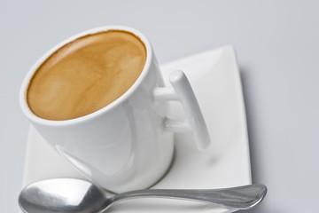 Café cremoso en una taza con platillo cuadrado.