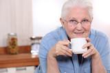 Elderly lady enjoying cup of tea in her kitchen
