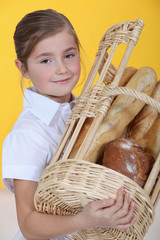 Little girl carrying basket of baguettes