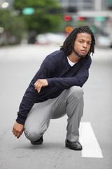 Man squatting in the street