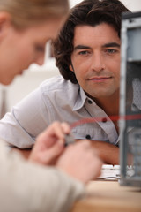 Man watching a woman repairing a television set