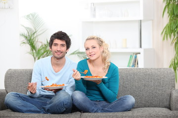 Couple having dinner on their couch