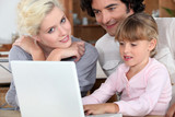 Couple with their daughter and a laptop