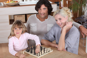 little girl playing chess with her parents