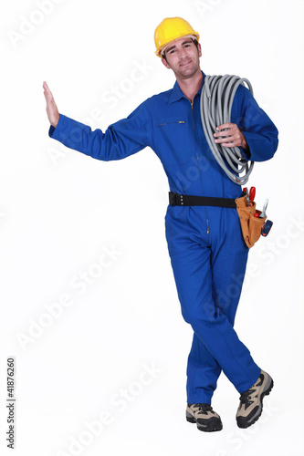 Electrician carrying spool of cable