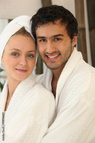 portrait of young couple all smiles wearing bathrobe