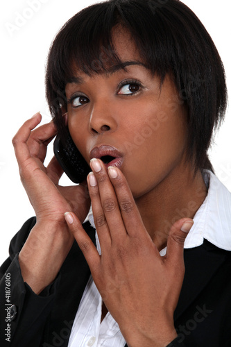 Afro businesswoman surprised on the phone