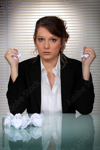 Angry woman scrunching up paper into balls