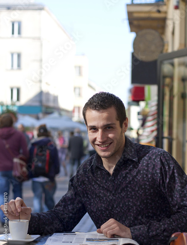 man drinking coffee on the street in restaurant