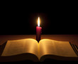 bible and candle in night