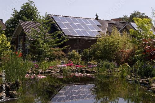 Haus mit Solarzellen und Teich
