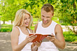 smiling couple dressed in white reading book