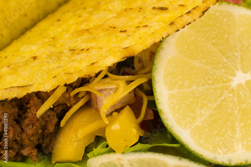 Close up of  Mexican minced beef tacos with salsa, cheese & lime