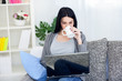 Woman drinking coffee while using laptop