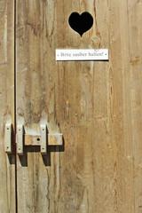 Herz in einer Holztür zum Plumsklo